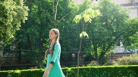 Glimlachend onbezorgd meisje met twee vlechtengangen en het stellen bij zonnig park stock videobeelden