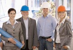 Glimlachend ontwerperteam dat bouwvakker draagt Stock Afbeeldingen