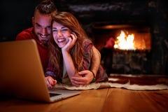 Glimlachend op vloer leggen en laptop met behulp van en paar die doorbladeren Stock Afbeeldingen