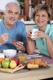 Glimlachend paar bij ontbijt Stock Foto