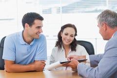 Glimlachend paar die contract met makelaar in onroerend goed ondertekenen Stock Foto