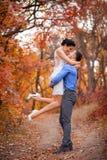 Glimlachend paar die in de herfstpark koesteren Gelukkige bruid en bruidegom in bos, in openlucht Royalty-vrije Stock Afbeelding