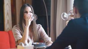 Glimlachend paar die diner hebben en witte wijn drinken op datum in restaurant stock footage
