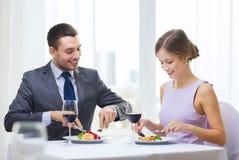Glimlachend paar die hoofdgerecht eten bij restaurant Royalty-vrije Stock Afbeeldingen
