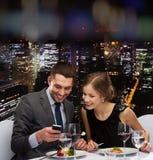 Glimlachend paar die hoofdgerecht eten bij restaurant Royalty-vrije Stock Foto's