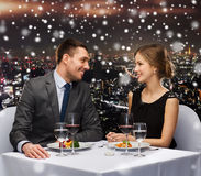 Glimlachend paar die hoofdgerecht eten bij restaurant Stock Afbeeldingen