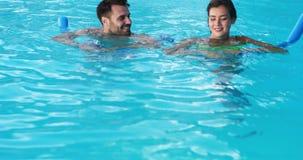 Glimlachend paar die met opblaasbare buizen zwemmen stock footage