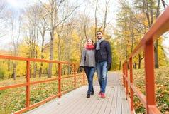 Glimlachend paar die op brug in de herfstpark koesteren Stock Foto's