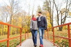 Glimlachend paar die op brug in de herfstpark koesteren Stock Afbeelding