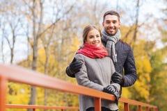 Glimlachend paar die op brug in de herfstpark koesteren Royalty-vrije Stock Foto