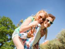 Glimlachend paar die pret en het tonen van overwinningsteken hebben Royalty-vrije Stock Afbeeldingen