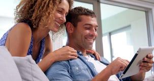 Glimlachend paar die tabletcomputer met behulp van stock video