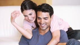 Glimlachend paar die terwijl het bekijken laptop omhelzen stock footage