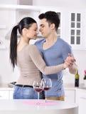 Glimlachend paar die van rode wijnstok in kitchev genieten stock foto