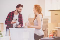 Glimlachend paar die verpakkings van materiaal genieten terwijl be*wegen-in nieuw huis stock foto