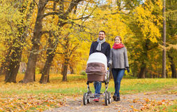 Glimlachend paar met babykinderwagen in de herfstpark Stock Afbeelding
