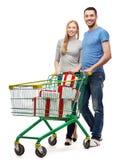 Glimlachend paar met boodschappenwagentje en giftdozen Royalty-vrije Stock Afbeeldingen