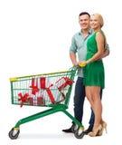 Glimlachend paar met boodschappenwagentje en giftdozen Royalty-vrije Stock Foto's