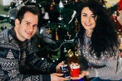 Glimlachend paar met de hete koppen van de chocoladeheemst royalty-vrije stock fotografie