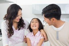 Glimlachend paar met een vrolijke dochter in keuken Stock Fotografie