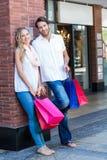 Glimlachend paar met het winkelen zakken die op de muur leunen Stock Foto