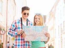 Glimlachend paar met kaart en fotocamera in stad Stock Foto's