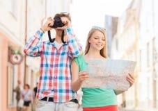 Glimlachend paar met kaart en fotocamera in stad Stock Fotografie
