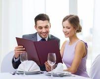 Glimlachend paar met menu bij restaurant stock fotografie