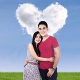 Glimlachend paar met wolken die van hart worden gevormd Stock Afbeelding