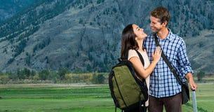 Glimlachend paar met zakken die op bergen reizen royalty-vrije stock afbeeldingen