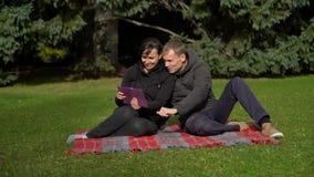 Glimlachend paar op het gras met tablet stock video