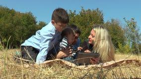 Glimlachend paar samen met kinderen die op park liggen stock video