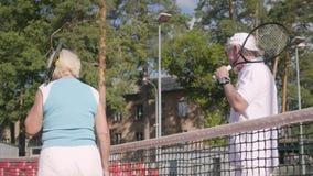 Glimlachend rijpe paar het schudden handen na het spelen van tennis op de tennisbaan Actieve vrije tijd in openlucht Hogere mens  stock video