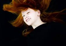 Glimlachend rood meisje in zwarte Stock Afbeelding
