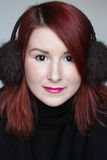 Glimlachend roodharigemeisje in het portret van oormoffen Stock Afbeelding