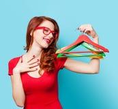 Glimlachend roodharigemeisje met hangers Stock Foto