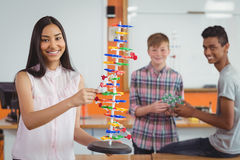 Glimlachend schoolmeisje die moleculemodel in laboratorium bestuderen Royalty-vrije Stock Afbeelding