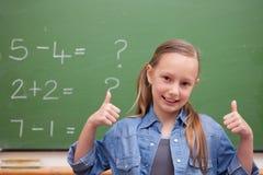 Glimlachend schoolmeisje met de omhoog duimen Royalty-vrije Stock Afbeelding