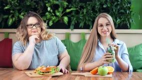 Glimlachend slank meisje en droevige vette vrouwenzitting in koffie samen snel voedsel versus gezonde maaltijd stock videobeelden