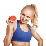 Glimlachend sportmeisje die de helft van grapefruit houden Stock Afbeelding