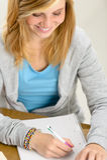 Glimlachend studentenmeisje die schrijvend op papier kijken Stock Foto