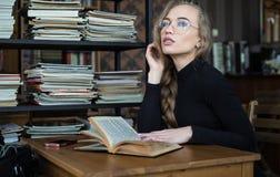 Glimlachend studentenmeisje in glazen in bibliotheek bestuderen en de dag die, denkt zij met hand bij kin en het kijken dromen royalty-vrije stock fotografie