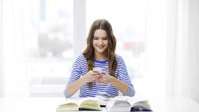 Glimlachend studentenmeisje met smartphone en boeken stock videobeelden