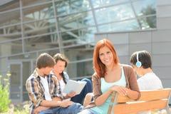 Glimlachend studentenmeisje met vrienden buiten universiteit stock afbeelding