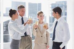 Glimlachend team van bedrijfsmensen die hun fluiten van champag clinking stock foto