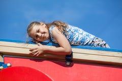 Glimlachend tien jaar oud meisjes bij de rode bouw van kinderenspeelplaats tegen blauwe hemel Stock Fotografie