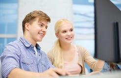 Glimlachend tiener en meisje in computerklasse royalty-vrije stock afbeelding