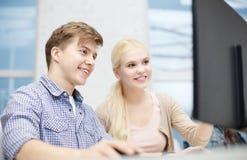 Glimlachend tiener en meisje in computerklasse royalty-vrije stock afbeeldingen