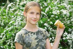 Glimlachend tienermeisje met roomijs in hand in de zomerpark stock afbeelding
