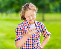 Glimlachend tienermeisje met smartphone Royalty-vrije Stock Foto's